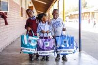 tres niños sonriente con sus mochilas nuevas